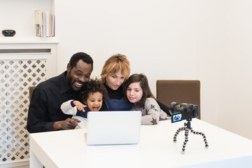 happy multi-ethnic family of vloggers uses a computer and a wirelessly connected camcorder to broadcast video on their blog, mixed-race couple with children use modern devices to connect to the world