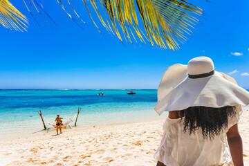 Jeune femme au chapeau de paille sur plage  du Morne, île Maurice