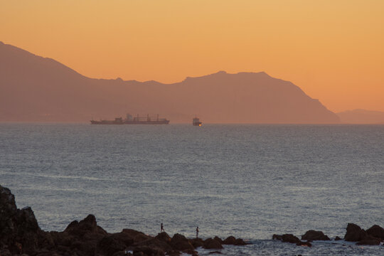 cargo ship crossing the sea at sunset