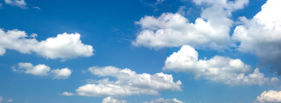 Wide banner with blue sky and white clouds.