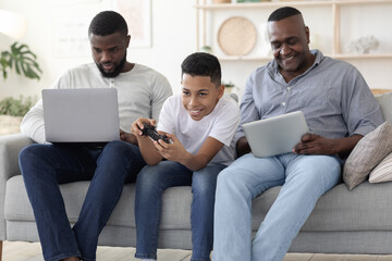 Male Family Pastime. Father, Son And Grandfather Spending Time With Different Gadgets