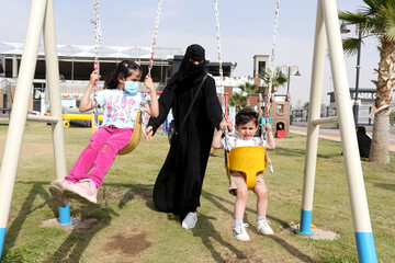 A Saudi woman is seen with her children at Abha Airport Park