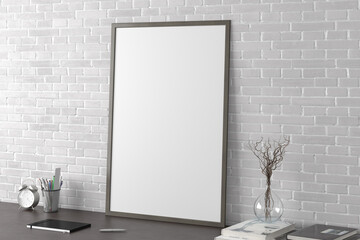 Vertical poster frame mockup on the black table of home studio workspace with white brick wall. Side view, clipping path around poster picture.