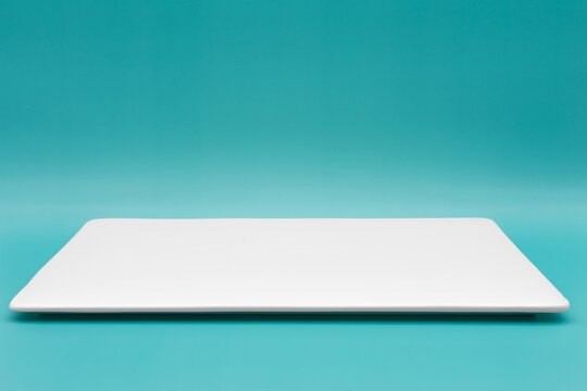 A rectangle empty white plate isolated on the tiffany blue background.