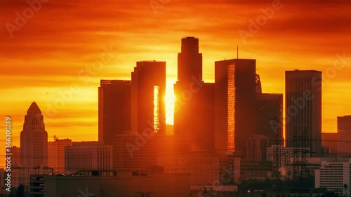 Fotobehang Sunset sun setting behind downtown Los Angeles skyline silhouette. Zoom out landmark city buildings. Timelapse, 4K UHD.
