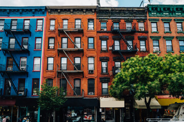 Houses from colourful bricks with residential and commercial real estate for rent in Brooklyn, beautiful vintage buildings with apartments and property for stores and shops on street in New York .