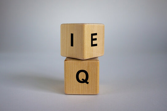 Wooden cubes with the expression 'IQ' 'Intelligence Quotient' to 'EQ' 'Emotional Intelligence Quotient'. Beautiful white background. Concept.