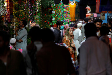 A man wearing face mask stands with sibling as they are shopping amid the rush of people along market, in Karachi