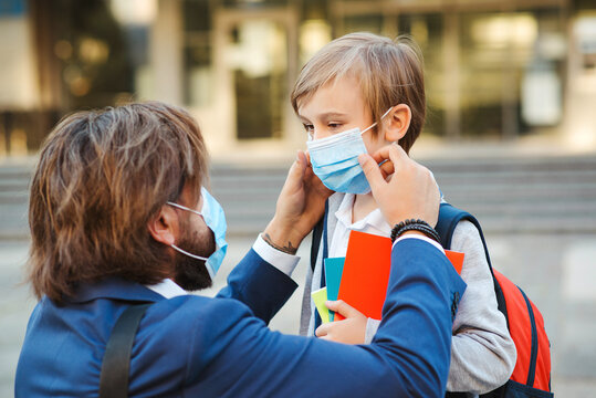 Father helping son and putting on face protective mask. Little boy going to school during coronavirus pandemic. Back to school 2020.