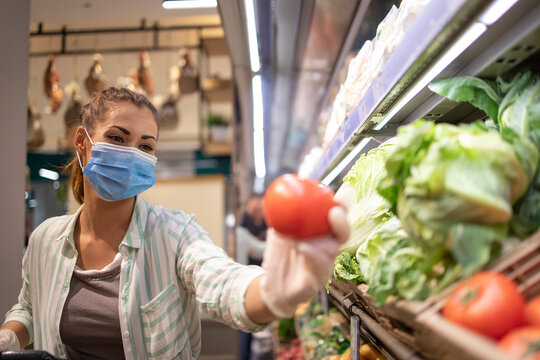 Woman with hygienic mask and rubber gloves and shopping cart in grocery buying vegetables during covid-19 and preparing for a pandemic quarantine.