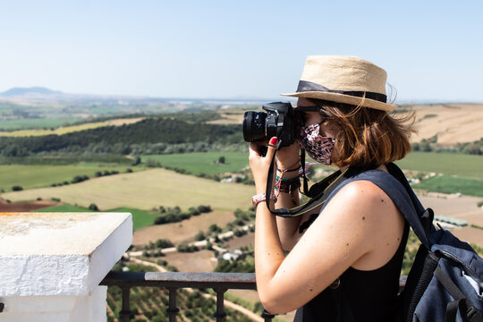 Attractive young female taking a picture with a reflex camera and visiting an old town while wearing a facemask during coronavirus pandemic