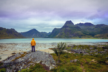 Fototapete - Panoramic view of the fjord. A young man stands on a rock. Beautiful mountain landscape. Scandinavian wilderness. Nature of Norway