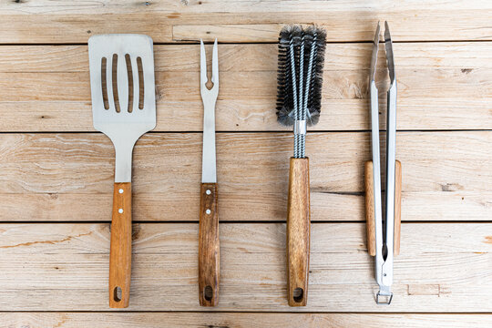 Set of Noble barbecue cutlery of acacia wood and stainless steel on a wooden table