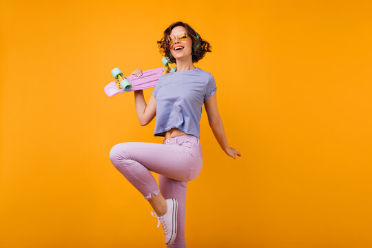 Slim stunning woman in summer attire having fun in studio. Indoor shot of pleased girl with brown hair holding skateboard and dancing.