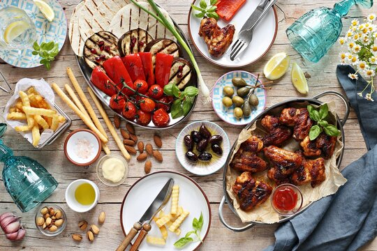 Chicken wings, roasted vegetables, grilled tortilla and appetizers variety serving on party outdoor table. Mediterranean dinner table concept. Overhead view.