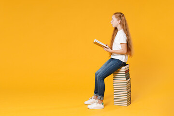 Full length young redhead girl 12-13 years old in white t-shirt jeans sit on big stack school...