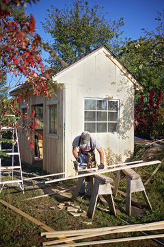Carpenter Man Using Circular Saw Building a Small Garden Cottage Shed