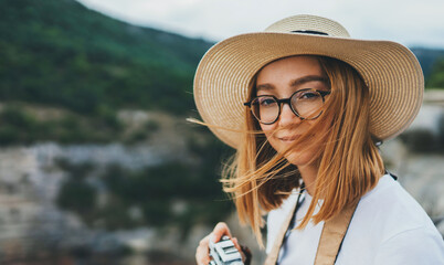 Wall Mural - portrait tourist girl in hat and glasses hold in hands retro camera walking in nature outdoor, blonde woman leisure vacation takes photos on backdrop of  landscape mountain, concept of travel vacation