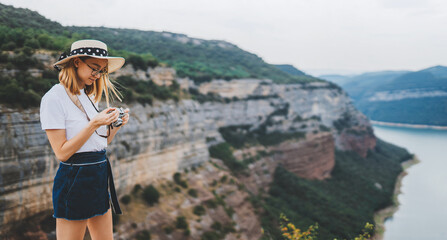 Wall Mural - blonde girl takes photo of  panorama landscape on camera during  trip on mountains outdoors, hipster tourist in summer hat enjoys hobby of photographing beautiful nature spain on weekend empty space