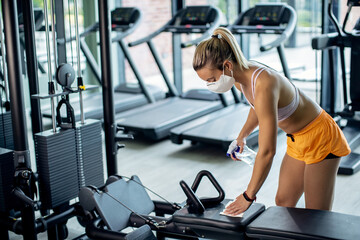 Sportswoman disinfecting exercise machine before working out in health club.