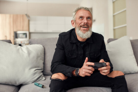 Up to the challenge. Bearded middle-aged man holding controller, playing video games, sitting on the couch at home. Weed vaporizer, dry herb vape pen lying next to him