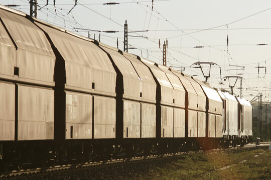 güterzug mit zwei elektrischen lokomotiven im flachen gegenlicht