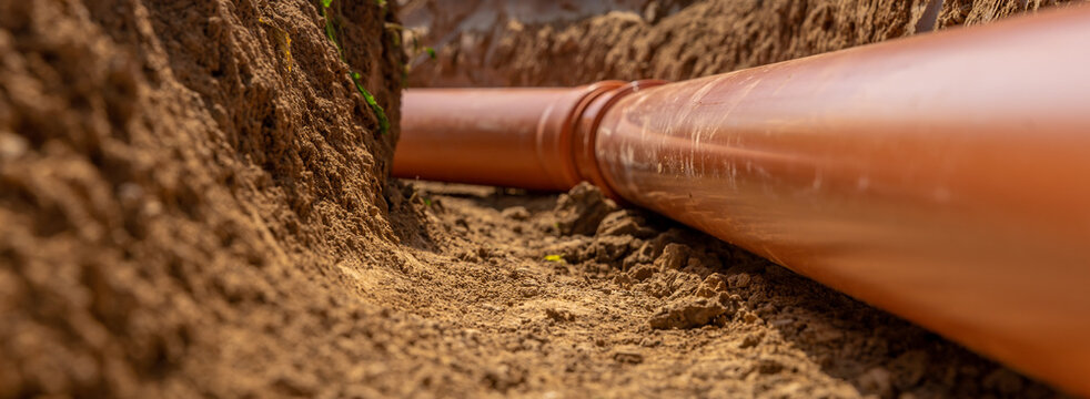 Plastic pipes in the ground during the construction of a building, bunner with copy space