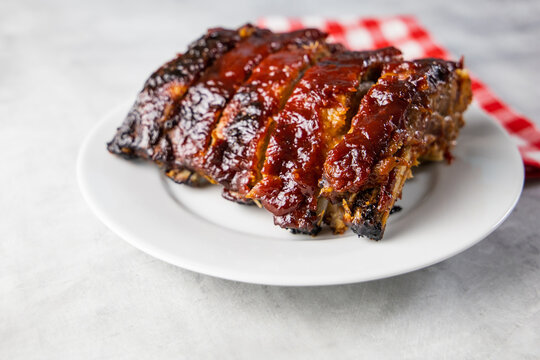 Oven-baked barbecue ribs with sauce on a white plate with a red checkered picnic napkin for a family barbecue
