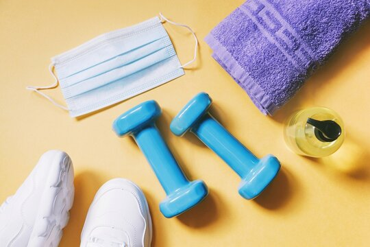 COVID-19 coronavirus post-lockdown. Resumption of work of fitness centers. Sports sneakers, dumbbells, blue disposable face mask, sanitizer gel and towel