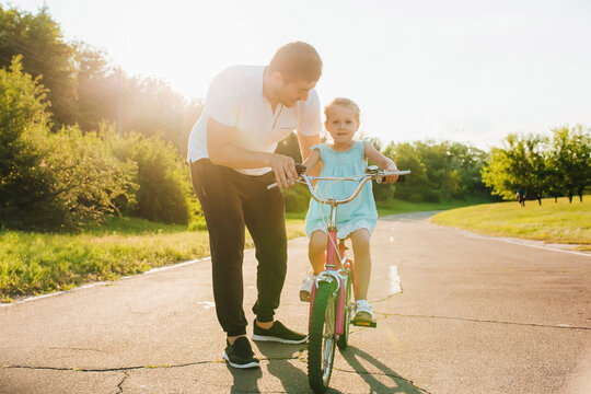 Dad is teaching daughter how to ride bicycle the street, Child learning to ride a bike. Family activities at summer.