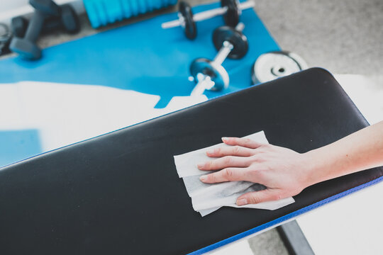 the new normal after covid-19, hand cleaning gym equipment with disinfectant wipe against virus and bacteria