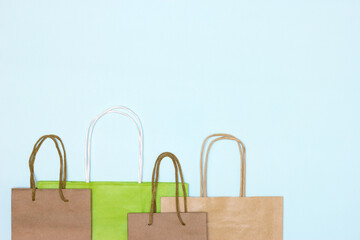 Craft paper merchandise bags on pastel blue background. Copy space. Shopping, sale minimal concept