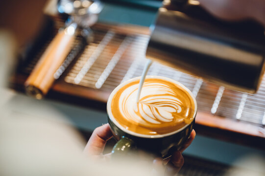 barista making latte art, shot focus in cup of milk and coffee, vintage filter image