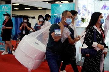 A man carries melt blown filter cloths at a procurement fair for epidemic-prevention materials in Shanghai