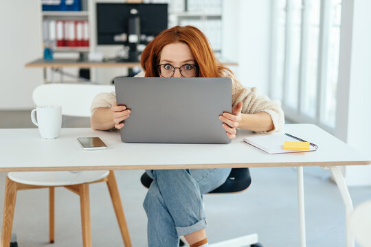 Young businesswoman staring aghast at laptop