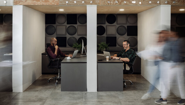 Two businessmen working in cubicles in a busy modern coworking office