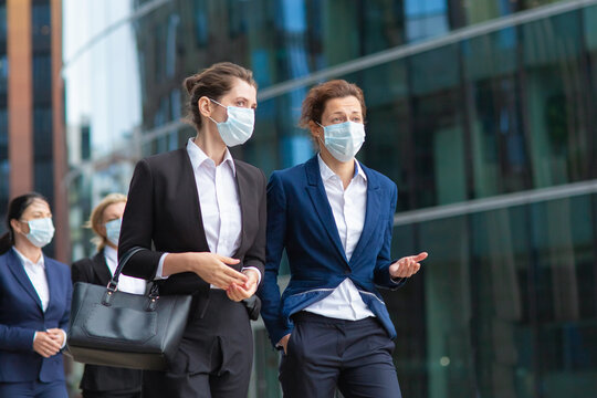 Female professionals wearing office suits and masks, meeting and walking together in city, talking, discussing project. Medium shot. Pandemic and business concept