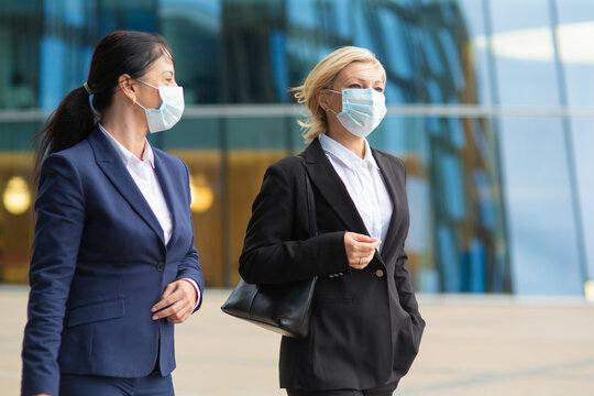 Business colleagues wearing office suits and masks, meeting and walking together in city, talking, discussing project. Medium shot. Business and coronavirus concept