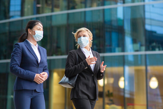 Businesswomen wearing office suits and masks, meeting and walking together in city, talking, discussing project. Medium shot. Business during epidemic concept