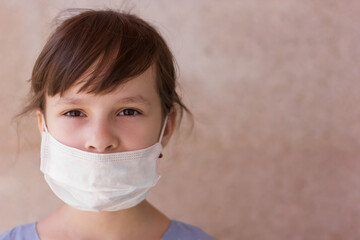 Photo sur Toile Doux monstres Portrait of a young girl in a medical mask isolated on a wall background. Young woman patient, copy space