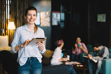 Half length portrait of cheerful young woman in casual wear standing with portable pc for work in office,prosperous female leader of professional satisfied with successful career looking at camera.