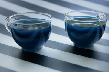 geometry composition, blue butterfly tea with milk on black and white