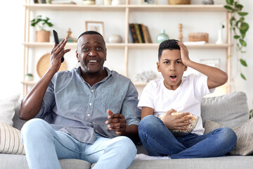 African Grandpa And Grandson Watching Sports On Tv, Emotionally Reacting To Score