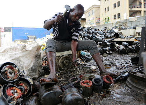 A man works on discarded compressors at a recycling centre in Abuja