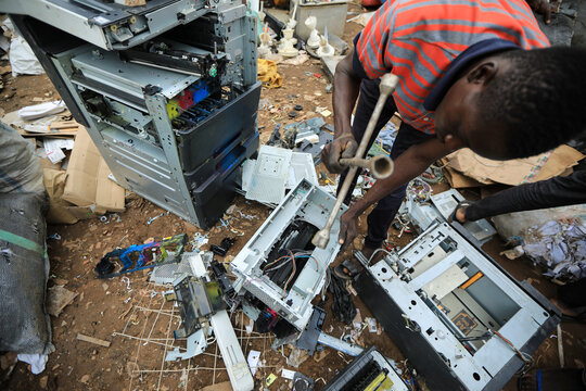 A man dismantles a printer at a recycling centre in Abuja