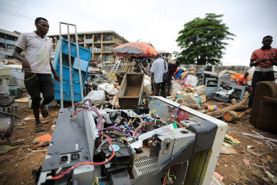 Men walk past discarded electronics items at a recycling centre in Abuja