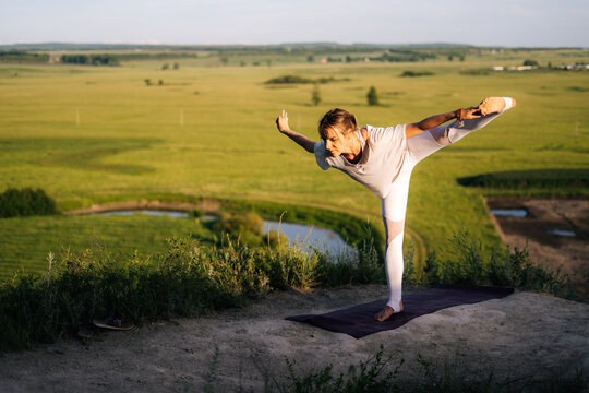 Sporty fit young woman practicing yoga on top of rock background of flowing river and green meadow on summer sunny day. Yogini girl performing Half Moon Pose. Lady practicing Ardha Chandrasana.