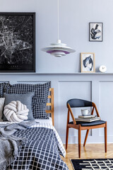 Stylish hipster bedroom interior with design chair, mock up poster frames, book, clock, decoration,...