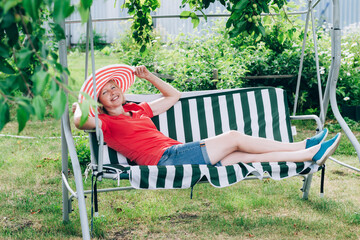 Cottagecore and Staycation at home. Happy elderly blonde woman in hat resting on swing. Relax in isolation