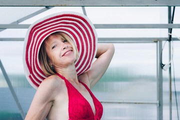 Cottagecore and Staycation at home. Happy elderly blonde woman in swimsuit and hat. Indoor home pool. Relax in isolation